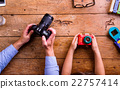 Father and son holding cameras, old wooden office 22757414