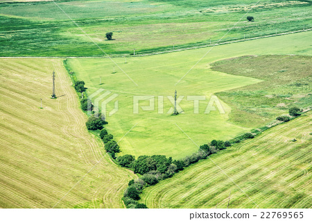 Green fields and high voltage power lines, view from airplane 22769565