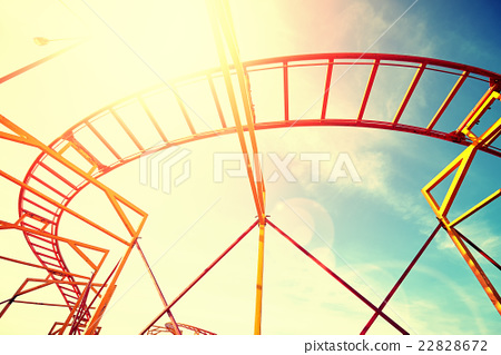 Vintage toned roller coaster rails against sun. 22828672