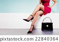 时尚形象。这款模特将脚与红色连衣裙和黑色高跟鞋结合在一起。你脚下的黑色手提包。 22840364