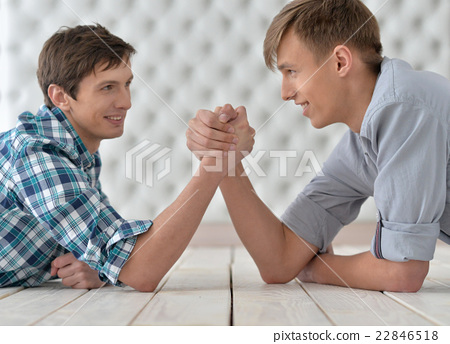 men  at the table and armwrestling  22846518