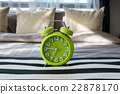 green alarm clock on bed in modern bedroom 22878170