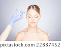 Doctor injecting botox into a woman's face 22887452