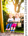 Two beautiful little girls swinging in the park. 22895988