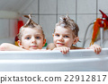 Two little boys playing together in bathtub 22912817