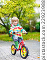 kid boy driving on bicycle on rainy day outdoors 22923988