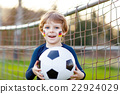Kid boy playing soccer with football  22924029