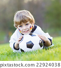 Kid boy playing soccer with football  22924038