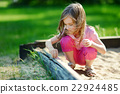 Adorable girl playing in a sandbox 22924485