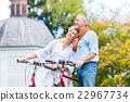 Seniors with bike in front of chapel or church 22967734