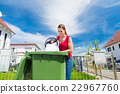 Woman throwing wastepaper in paper bin 22967760