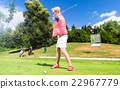 Senior woman doing tee stroke on golf course 22967779