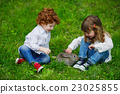 boy and girl playing with rabbit 23025855