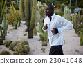Young fit man in white windbreaker running fast  23041048