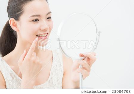 一個女人看著鏡子(牙科護理) 23084708