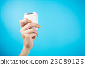 Woman holding epilator against blue background 23089125
