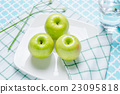 Fresh green apples in a dish on table. 23095818
