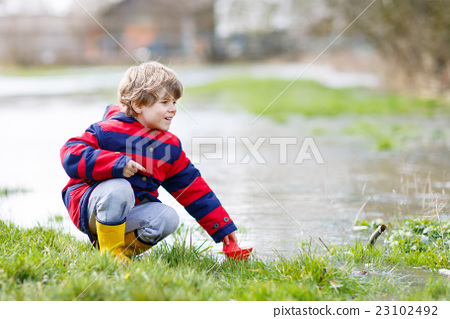 Little kid boy playing with paper boat by puddle 23102492