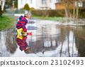 Little kid boy playing with paper boat by puddle 23102493