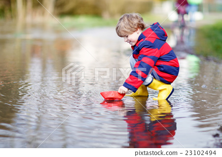 Little kid boy playing with paper ship by puddle 23102494