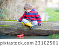 Little kid boy playing with paper boat by puddle 23102501