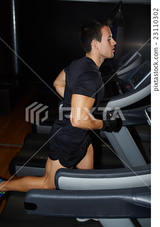 Fit man running in a gym on a treadmill  23110302