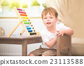 Little boy playing with abacus toy indoors 23113588