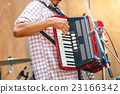 Close up musicians are playing accordion on stage 23166342