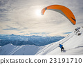 Paraglider launching from snowy slope 23191710
