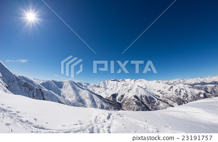 Stock Photo: Sun star glowing over snowcapped mountain range, italian Alps