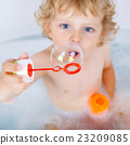 toddler boy playing with soap bubbles in bathtub  23209085