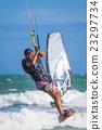 Athletic man riding on kite surf board sea waves 23297734