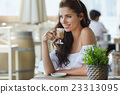 Portrait of beautiful blond woman sitting in outdoors cafe in It 23313095