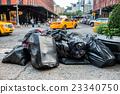 Black bags of trash on sidewalk in New York City  23340750