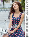 Young  italian woman sitting on a vintage scooter 23351044