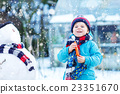 Funny kid boy making a snowman in winter outdoors 23351670