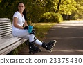 Beautiful girl on roller skates in park sits on bench and drinks water 23375430