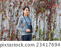 Asian woman with binoculars over ivy wall 23417694