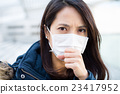 Woman wearing medical face mask 23417952