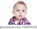 A boy with a hearing aids on gray background 23450416