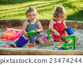 The two little baby girls playing toys in sand 23474244