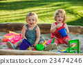 The two little baby girls playing toys in sand 23474246