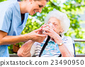 Geriatric nurse giving glass of water to senior  23490950