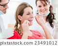 Woman at dentist using dental floss 23491012