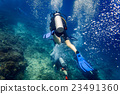 Air bubbles emerging from diver at coral reef  23491360