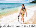Woman with snorkelling gear walks on beach 23491369