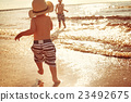 Two brothers are walking on the beach 23492675