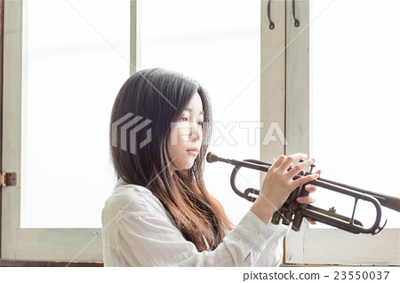 A beautiful Japanese woman practicing trumpet 23550037