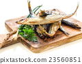 Wooden board with smoked fish and parsley close-up 23560851