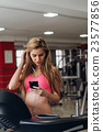 Blonde with a phone  at the gym. Listening to 23577856